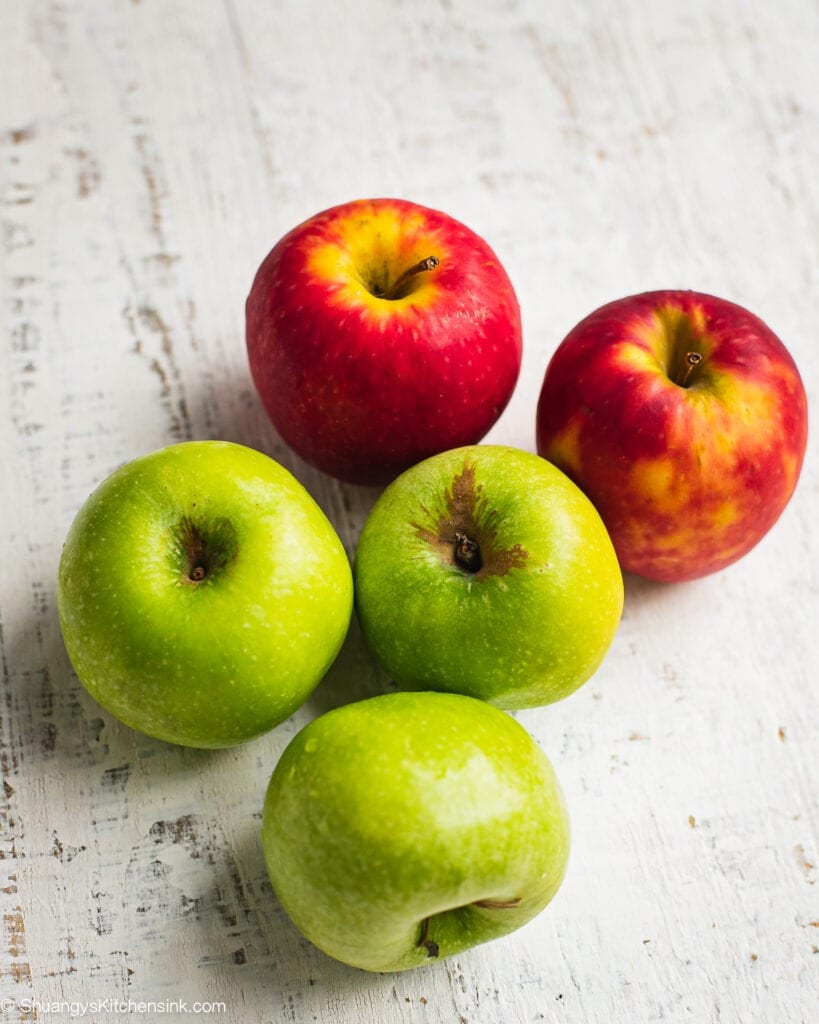 5 apples on a wooden table. There are three granny smith apples and 2 Pink Lady apples.