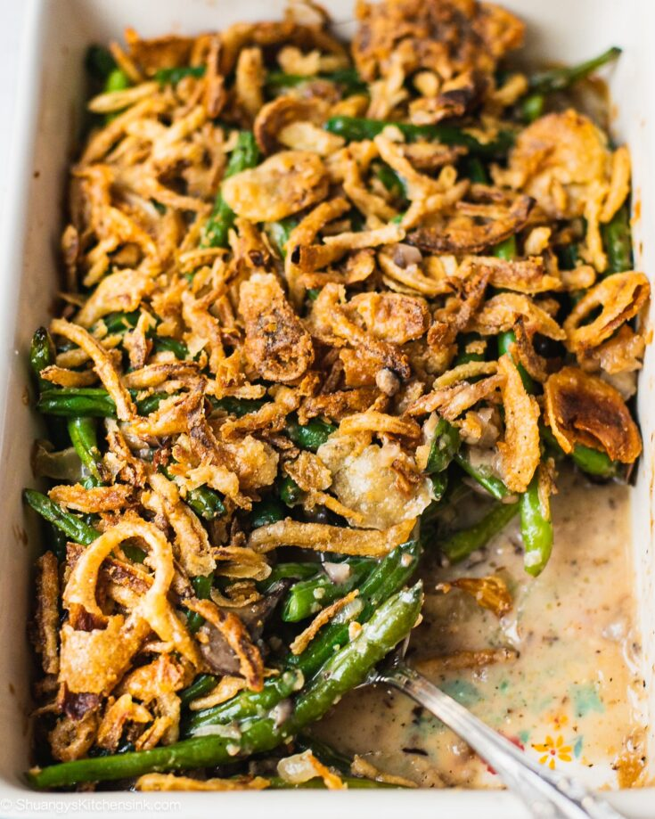 A pan of easy green bean casserole that has gluten free crispy onion on top, and cream mushroom soup with baked green greens.