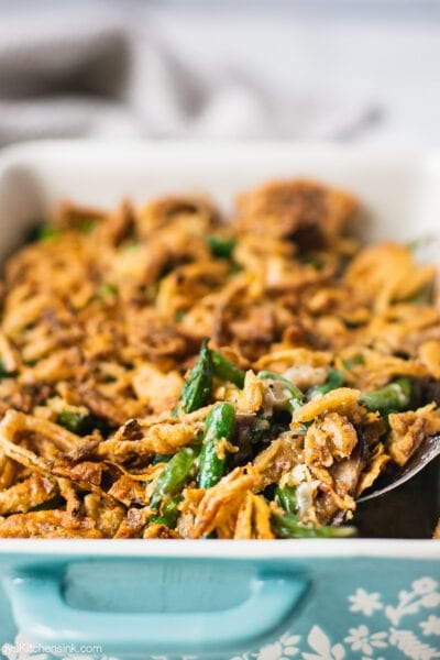 A pan of freshly baked healthy green bean casserole topped with golden brown gluten free crispy onion.