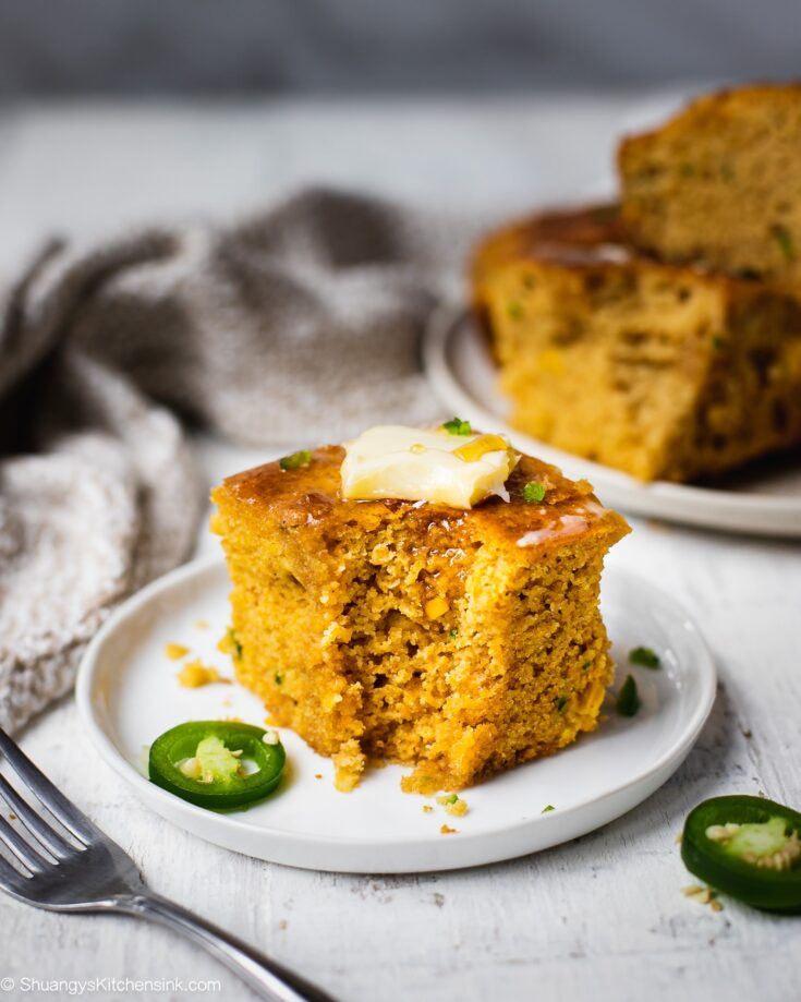 A slice of honey jalapeños cornbread that is gluten free and dairy free. Optional toppings to make it a delicious honey butter cornbread. There is another plate of cornbread in the back.