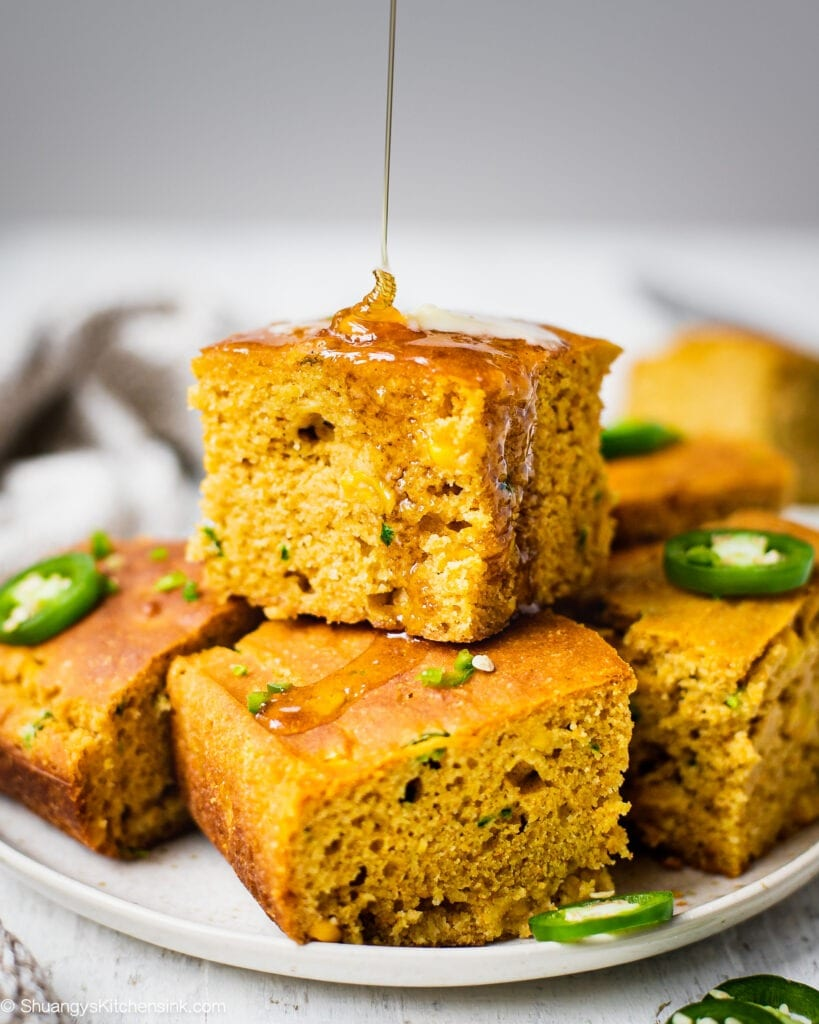A plate of healthy cornbread made sweet honey and spicy jalapeños. The texture appears to be fluffy and moist. Topped with vegan butter that is dairy free.