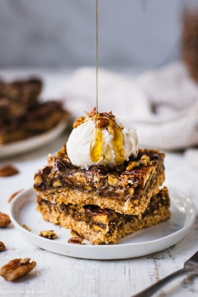 Two pieces of pecan pie bars on a plate. A rich caramel pecan pie filling on top of paleo almond flour crust, it is served with a scoop of vanilla ice cream and vegan caramel sauce.