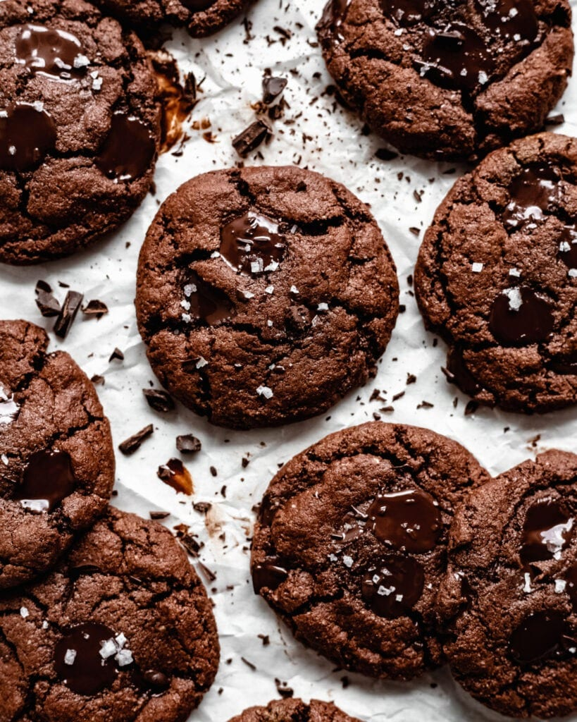 A batch of freshly baked vegan double chocolate chip cookies. It looks soft and brownie-like with melted dark chocolate chips on top and a sprinkle of sea salt.