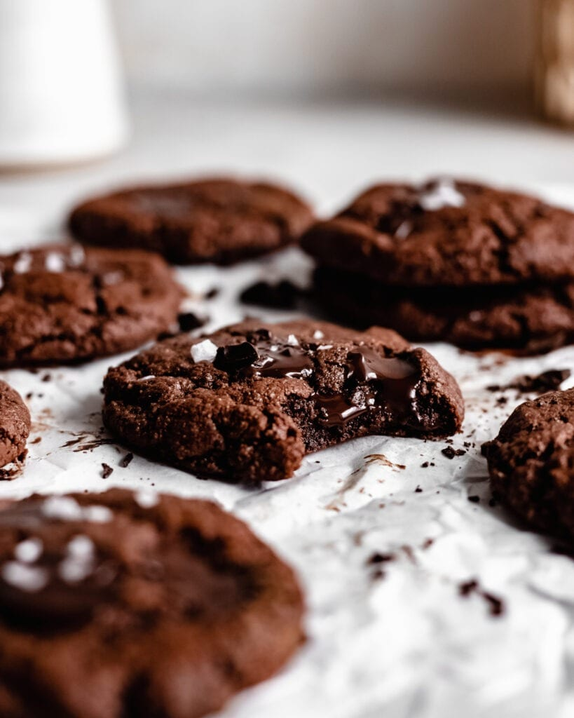 A batch of freshly baked vegan double chocolate cookies. It looks soft and brownie-like with melted dark chocolate chips on top and a sprinkle of sea salt.