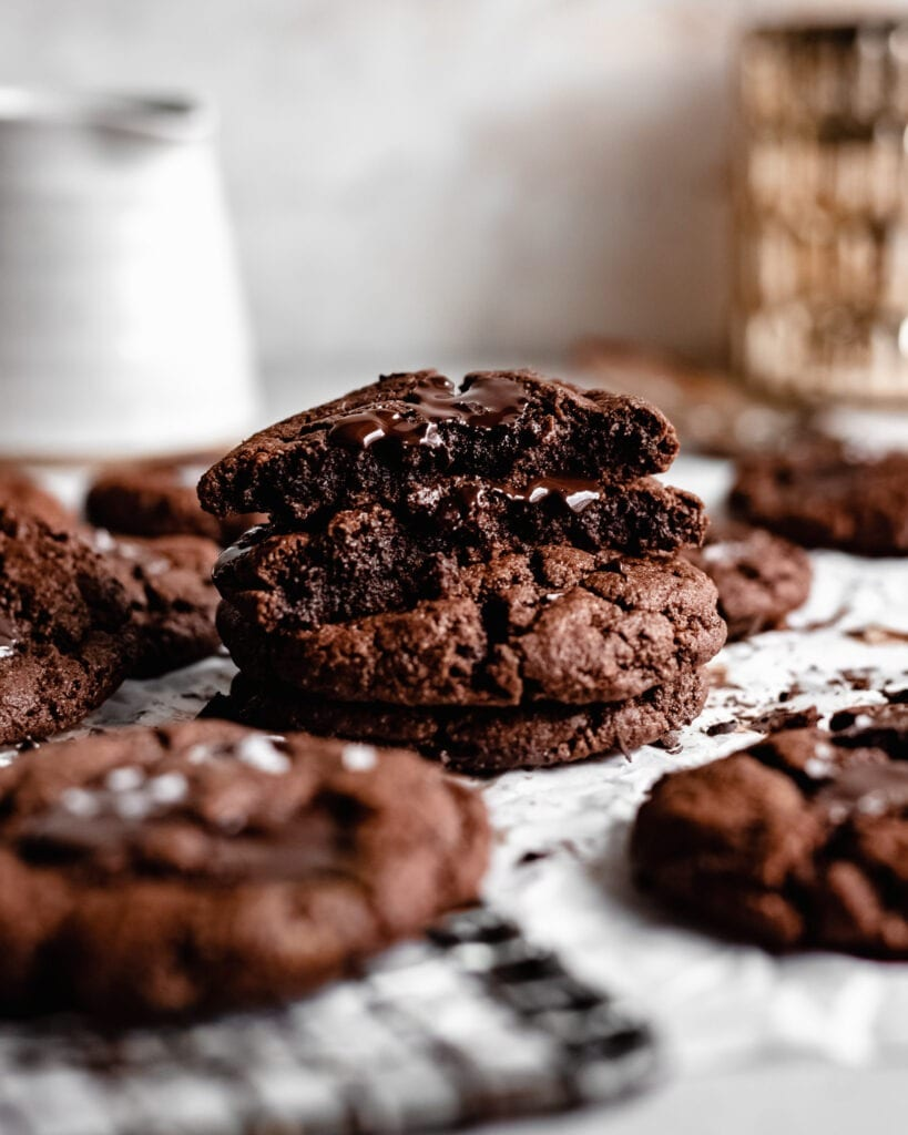 A stack of gluten free chocolate cookies. The top one has a bite in it, the texture appears to be soft and brownie-like.