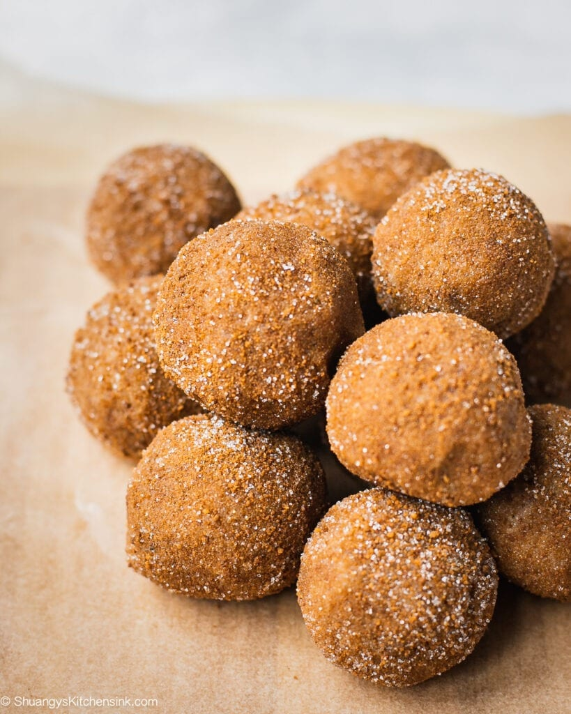 A batch of snickerdoodle no bake energy bites on a piece of parchment paper. These vegan protein balls are rolled in cinnamon sugar coating.