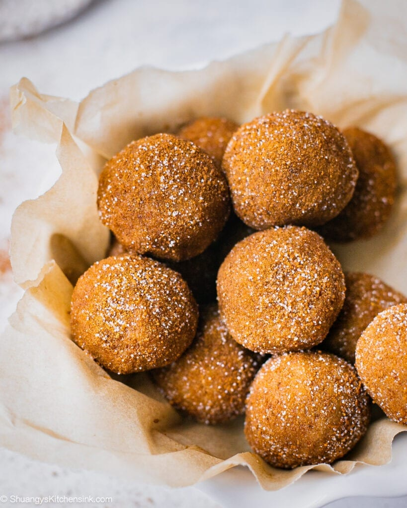 A batch of snickerdoodle no bake energy bites in a bowl. These vegan protein balls are rolled in cinnamon sugar coating.