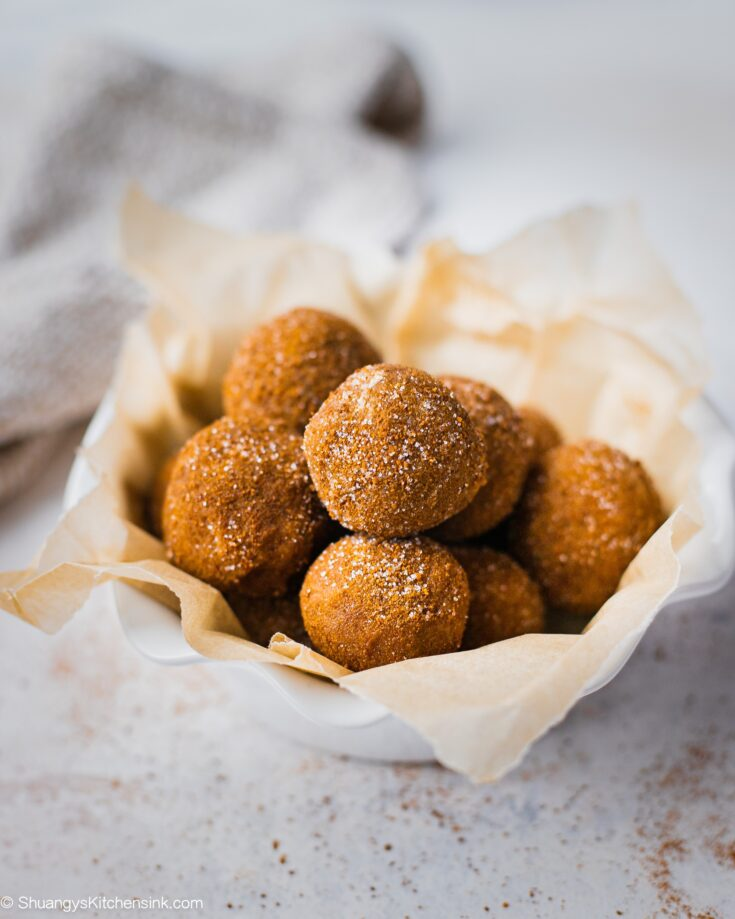 A batch of snickerdoodle energy bites in a bowl. These vegan protein balls are rolled in cinnamon sugar coating.