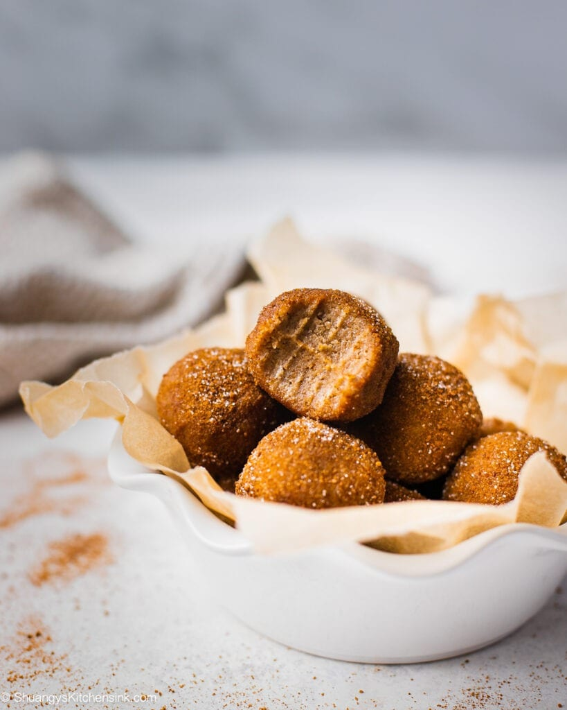 A batch of snickerdoodle energy bites in a bowl. The one on top has a bite in it, the texture appears to be gooey and chewy.