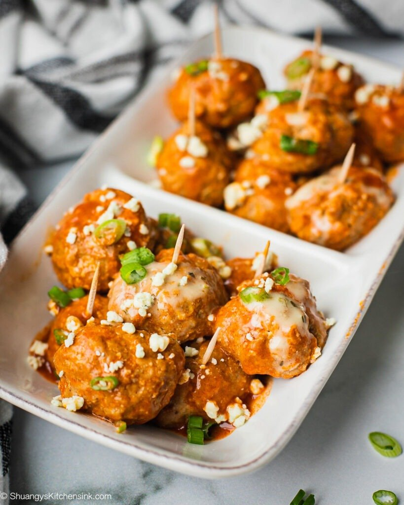 A serving dish of healthy buffalo chicken meatballs topped with scallions, blue cheese and ranch dressing.
