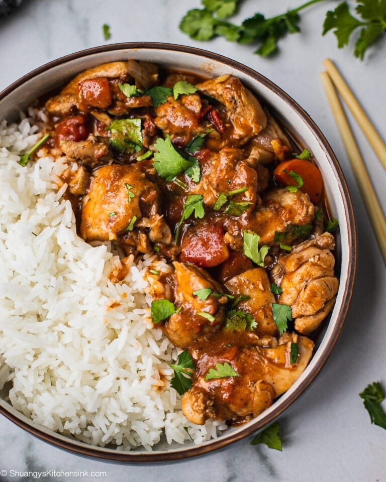 A bowl of healthy instant pot butter chicken that has tender and juicy chicken, indian spices and silky coconut milk. It is served with rice on the side and cilantro on top.