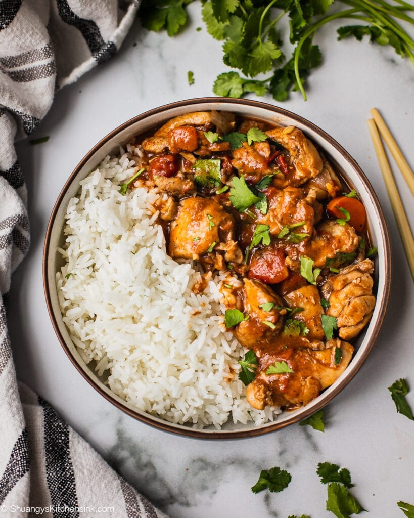 A bowl of healthy instant pot butter chicken that has tender and juicy chicken, indian spices and silky coconut milk. It is served with rice on the side and cilantro on top. This is a great freezer meal for new mmoms