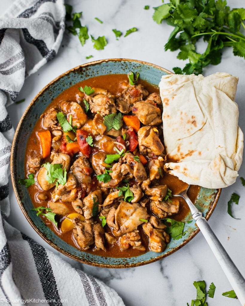 A plate of keto butter chicken that is cooked in flavorful Indian Spiced sauce in the instant pot. It has cilantro on top for garnish. it is served with gluten free naan bread.