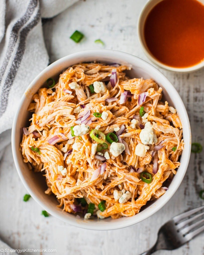 A bowl of instant pot buffalo chicken ready to be served. This buffalo shredded chicken is topped with blue cheese, scallion and red onion. There is whole30 friendly buffalo sauce on the side.
