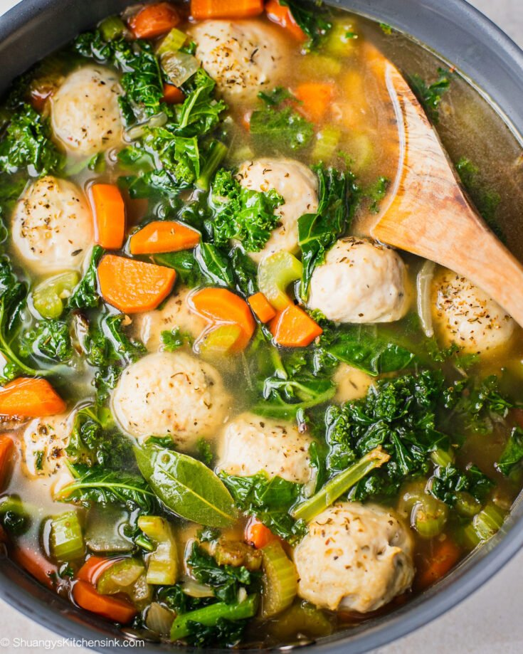 A pan of stove top gluten free dairy free soup using this easy Italian Wedding Soup recipe. There are baked chicken meatballs, celery, kale and carrots.