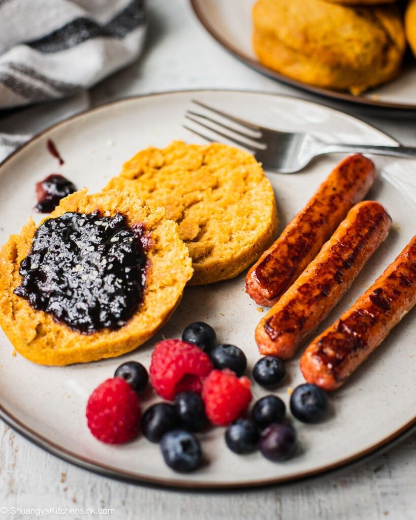 A plate of healthy plant based breakfast with gluten free vegan biscuits, fresh berries and vegan breakfast sausage.