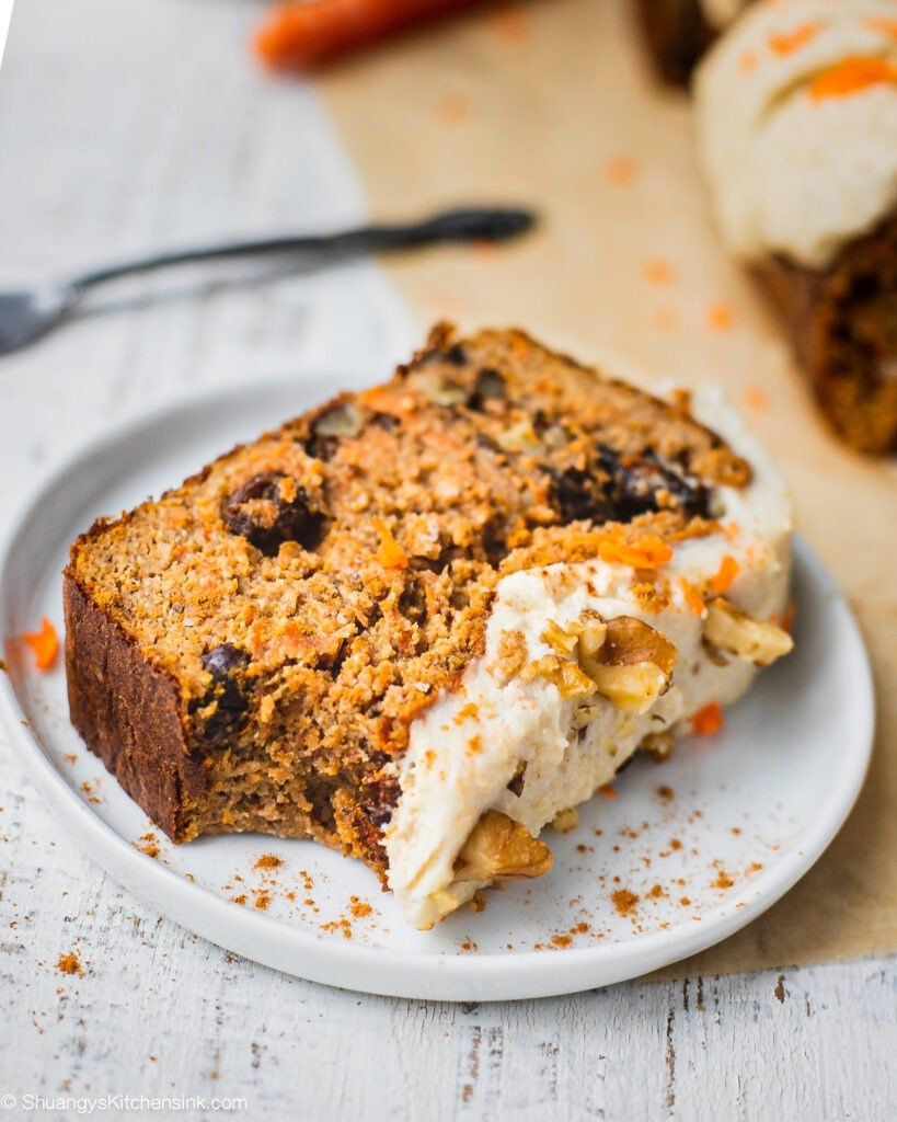 A piece of carrot cake bread with dairy free cream cheese frosting on top. There is a bite in this healthy and moist carrot cake loaf.
