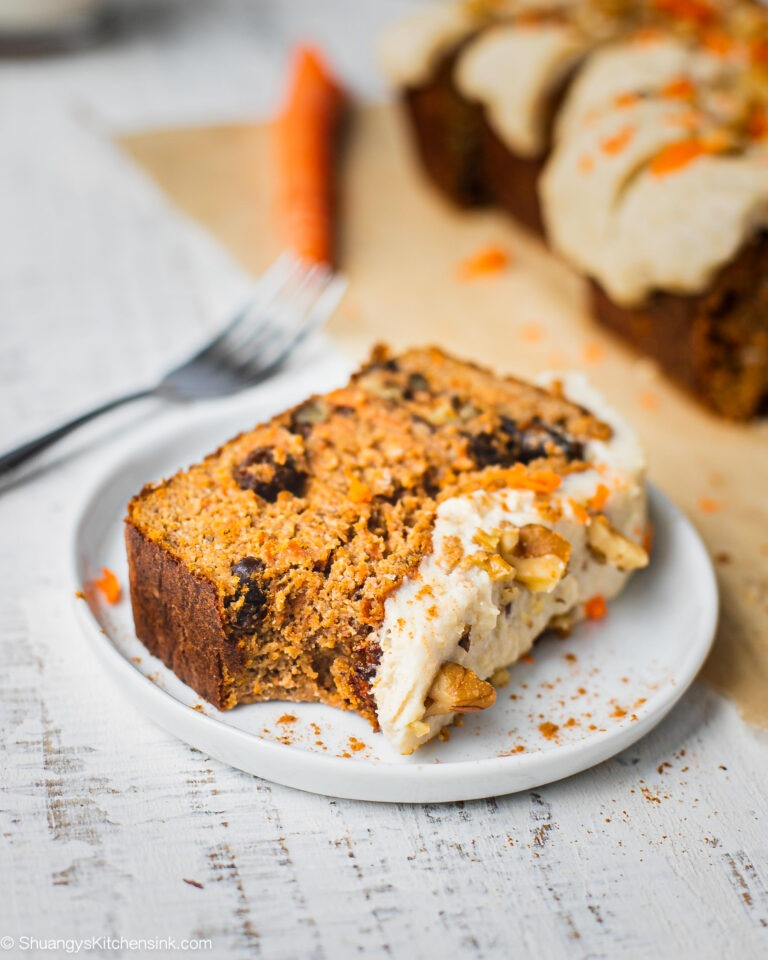 A piece of carrot cake banana bread with cashew cream cheese frosting that is dairy free. This carrot cake loaf recipe is paleo, gluten free and easy to make.