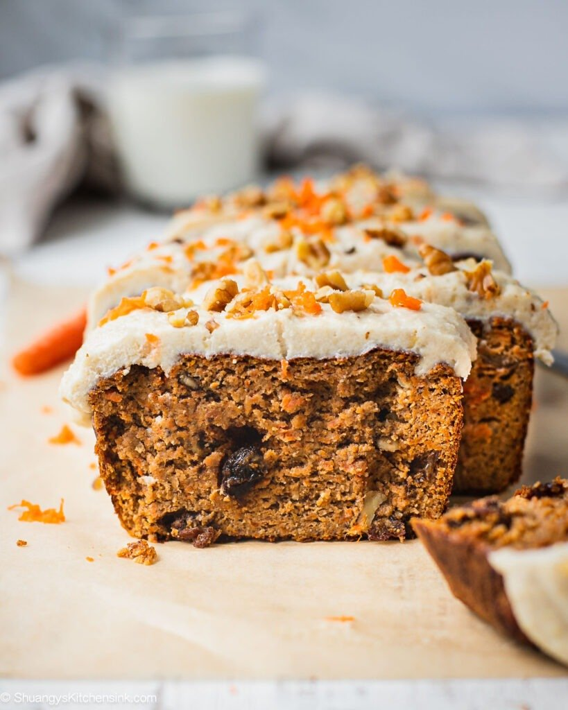A loaf of carrot cake banana bread with cashew cream cheese frosting on top. There are walnuts and raisins in the middle of this carrot cake bread and shredded carrots on top.