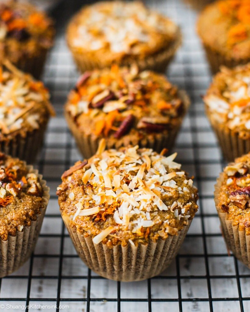 A batch of freshly baked paleo carrot muffins that are topped with shredded coconut and pecans.