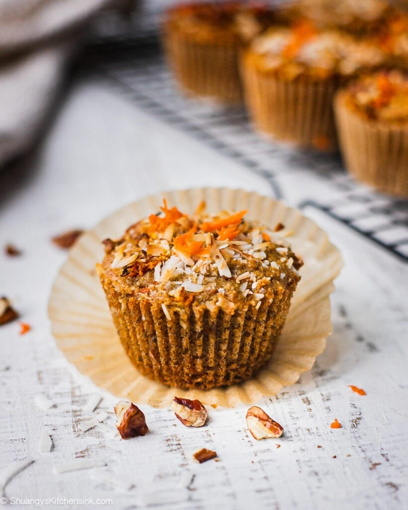 A healthy carrot cake muffin has a bite in it. It is topped with shredded coconut, chopped pecans and carrots. The texture appears to be soft and fluffy.