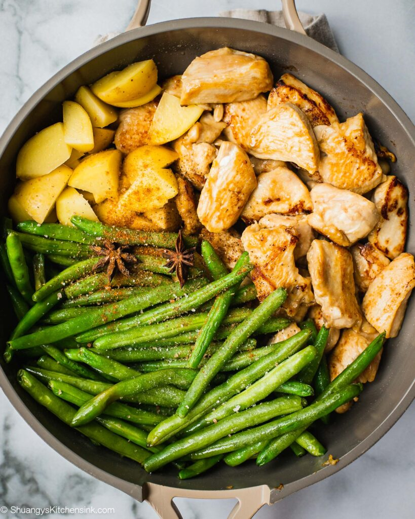 A pan of chicken green beans and potatoes seasoned with healthy and authentic Chinese spices.