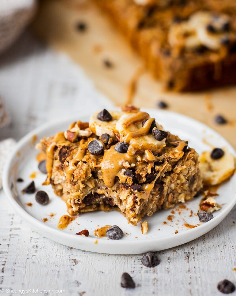 A piece of peanut butter banana oatmeal bar is topped with banana, peanut butter chocolate chips. There is a bite in the middle of this peanut butter oatmeal bar and the texture appears to be soft and chewy.