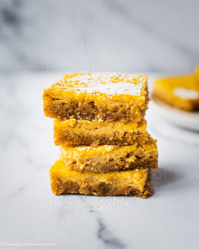 A stack of healthy lemon bars with a paleo and gluten-free buttery crust. There is powdered sugar on top of the lemon bars to serve.
