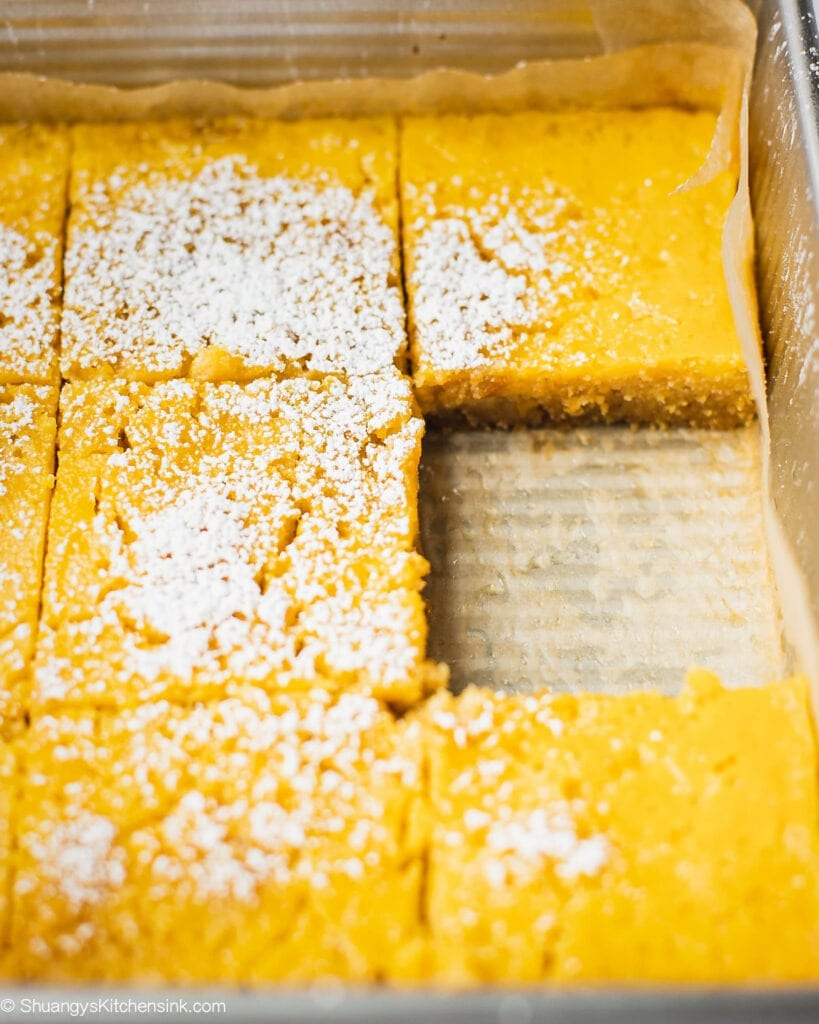 A pan of healthy lemon bars that are paleo and gluten free. These sweet and tangy lemon bars are served with powdered sugar.