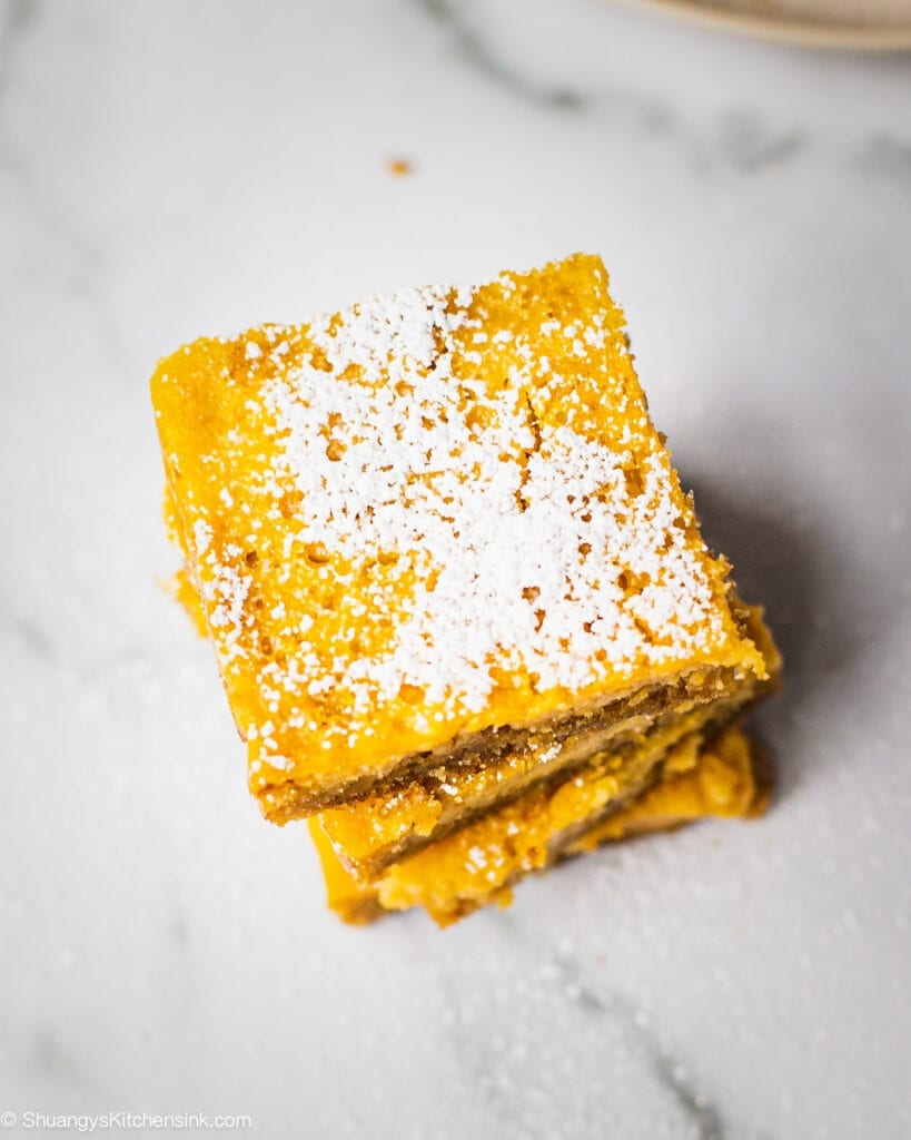 A stack of healthy lemon bars that are paleo and gluten free. These sweet and tangy lemon bars are served with powdered sugar.
