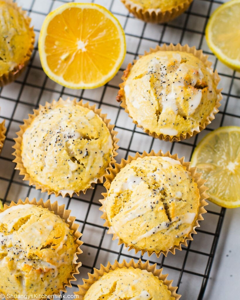 A batch of gluten-free lemon poppyseed muffins on a cooling rack. There is coconut icing on the healthy lemon poppyseed muffins.