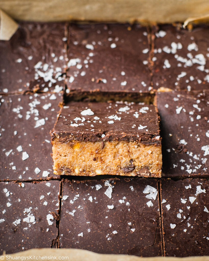 There is a tray with freshly cut cheesecake bars that are topped with a vegan ganache and a sprinkle of sea salt. It's a tray of nine bars and the middle cheesecake bar is lifted up to display the gooey nut and date layer.