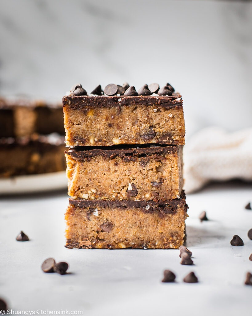 Three gluten-free no-bake cheesecake bars are stacked on top of each other and shot from the side. You can see the different layers of a nutty crust, gooey date filling and a smooth chocolate top.