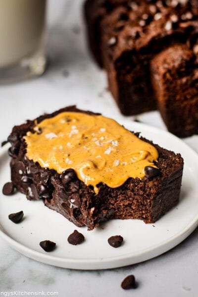 A piece of gluten free banana bread chocolate chips on a plate served with a glass of milk.