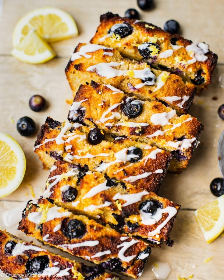 A loaf of sliced healthy blueberry lemon bread with coconut butter.