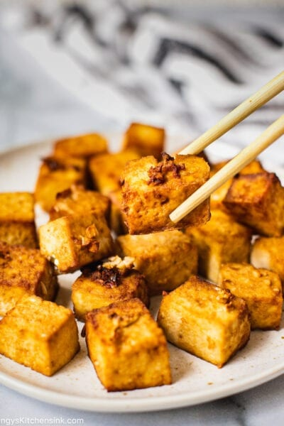A plate full of air fried crispy tofu. One piece is being picked up by chopsticks