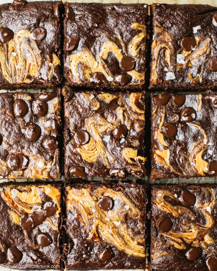nine squared of healthy banana brownies shot from above. The gluten free chocolate dessert is swirled with nut butter