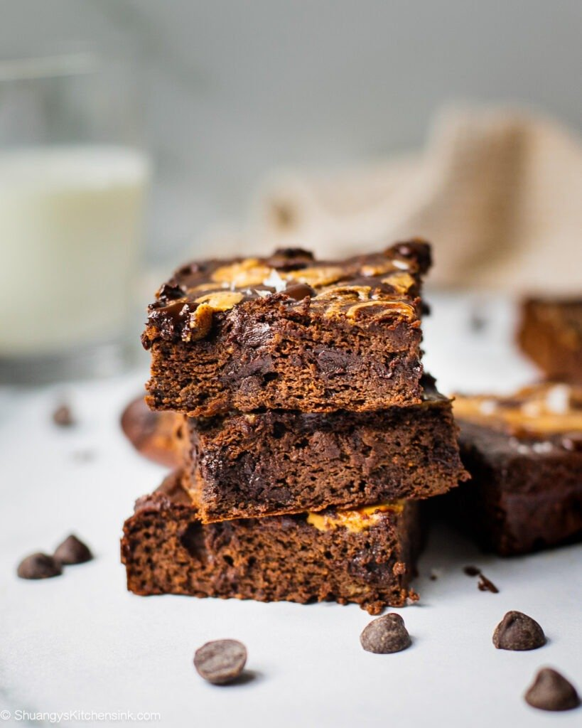three chocolate banana brownies stacked on top of each other. Chocolate is oozing out and extra chocolate chips are sprinkled everywhere.