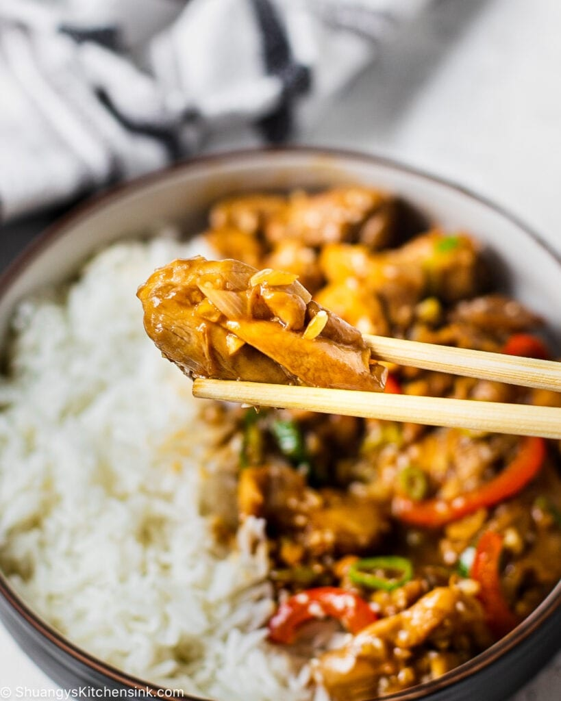 One piece of chicken is about to get eaten using chopsticks. In the background you can see a bowl of rice and fresh vegetables.