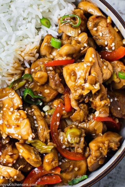 A bowl of jasmine rice and Healthy Chinese Garlic Chicken. There are red peppers and green scallions as well and a sprinkle of sesame seeds
