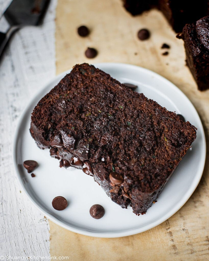 A slice of Zucchini Chocolate Chip Bread that is soft and moist. There is more gluten free chocolate zucchini bread in the background.