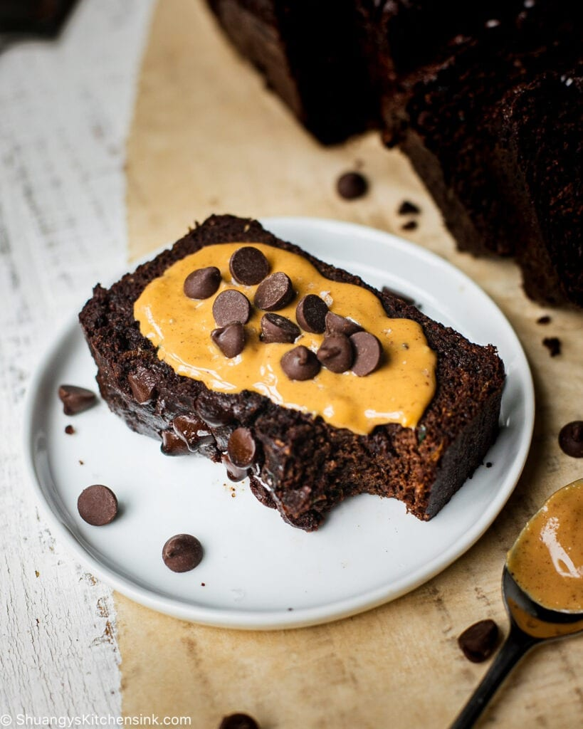 A slice of healthy chocolate zucchini bread served with nut butter and chocolate chips.