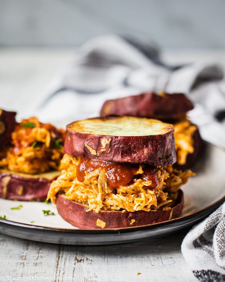 A plate of Whole30 BBQ pulled chicken that is cooked in the instant pot in 15 minutes. Served with Sweet potato buns for a Paleo and WHole30 friendly dinner recipe.
