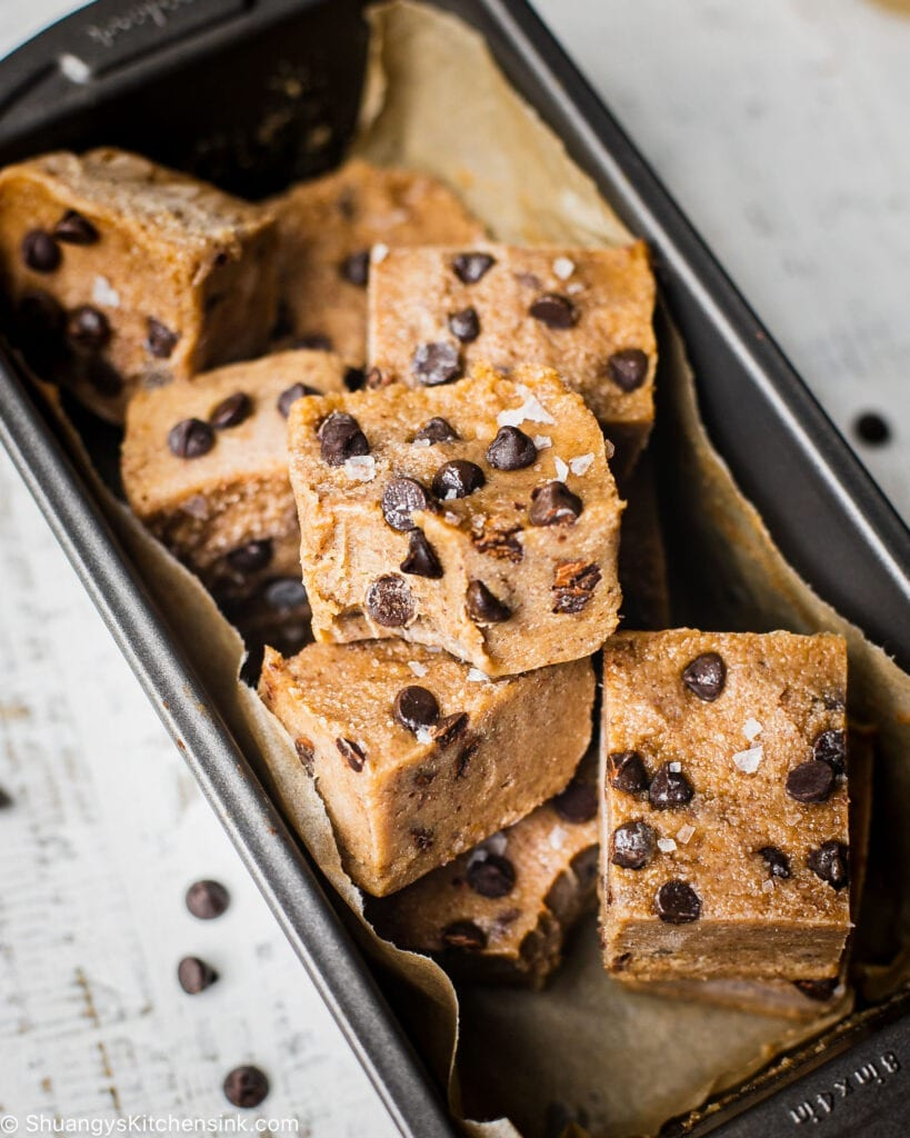 There are a pile of fudgy no bake cookie dough bites topped with dairy free chocolate chips and flaky salt