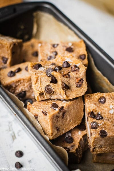There are a pile of fudgy gluten free no bake cookie dough bites topped with dairy free chocolate chips and flaky salt
