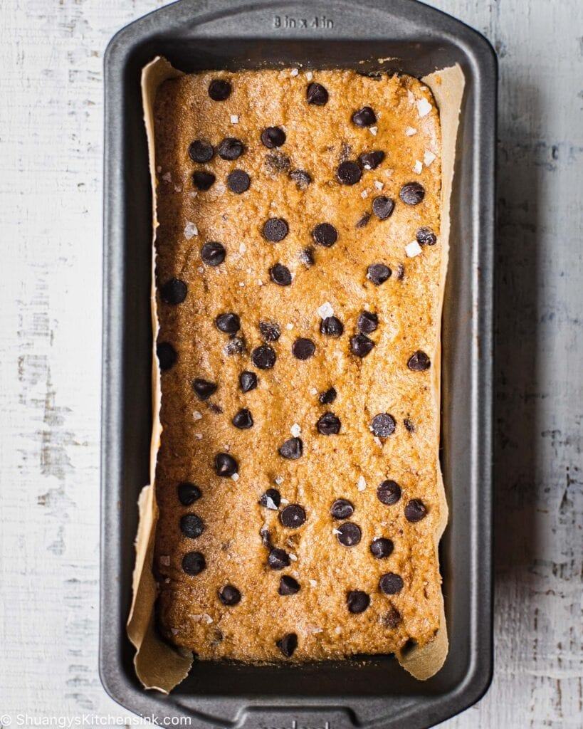 a loaf pan with vegan cookie dough topped with gluten free chocolate chips and flaky sea salt