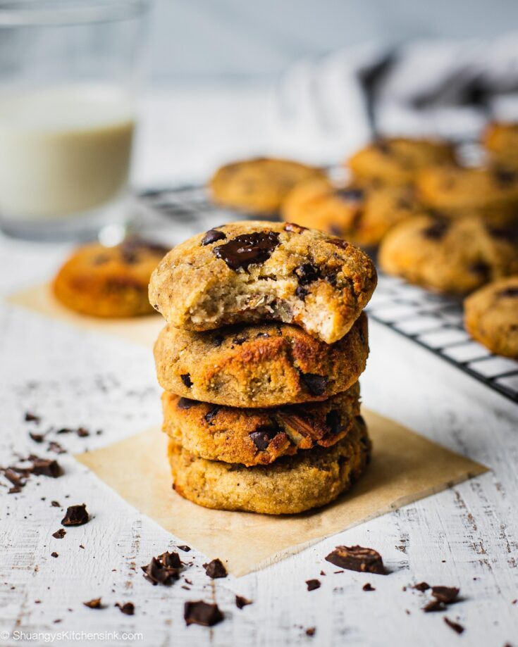 four banana bread cookies are stacked on top of each other in front of more gluten free cookies . Someone has already taken a bite from the top cookie
