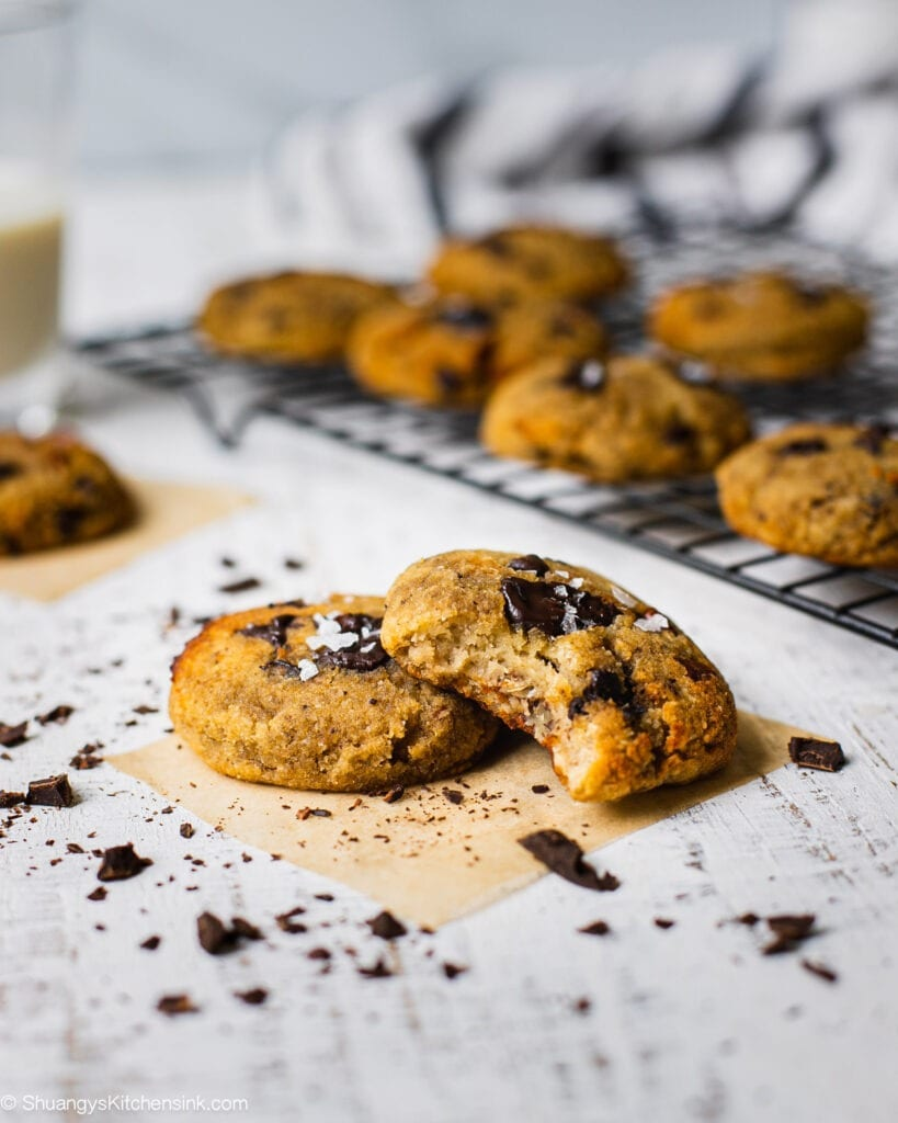 two cookies on a counter top. Someone has taken a bite from one of the gluten free and egg free cookies. These are vegan chocolate and sea salt on the cookies. In the background there are more cookies on a cooling wrack.