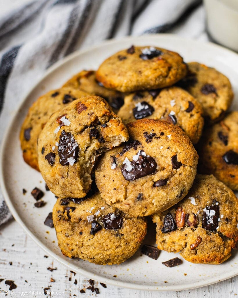 A round plate with golden brown healthy cookies on it. the cookies has cocolate chips and sea salt on them.