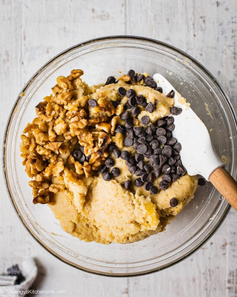 Walnuts and vegan chocolate chips being folded into banana cookie dough